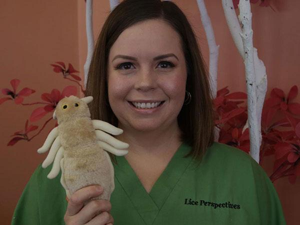 Krystal in green scrubs with a stuffed lice toy.