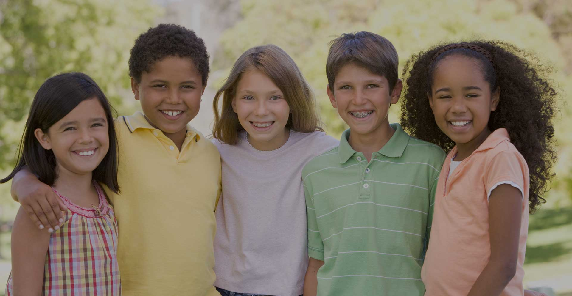 Five children standing in a row in a park smiling at camera